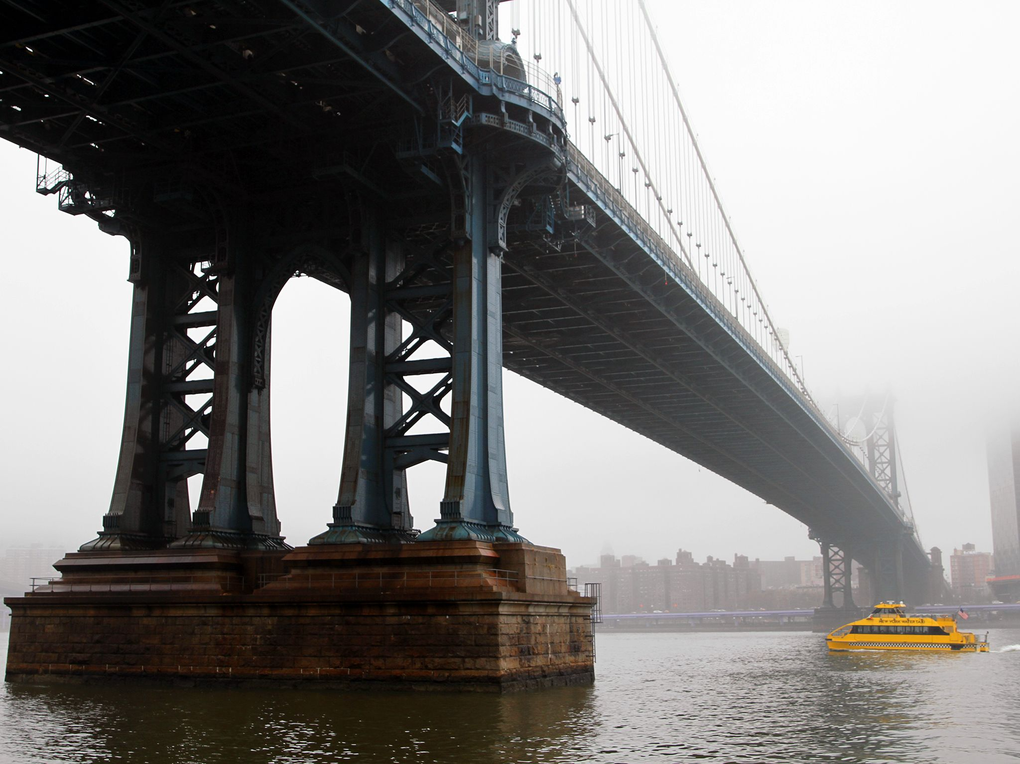 A New York Water Taxi passes under Manhattan Bridge as fog encloses the city. This image is from... [Photo of the day - April 2020]