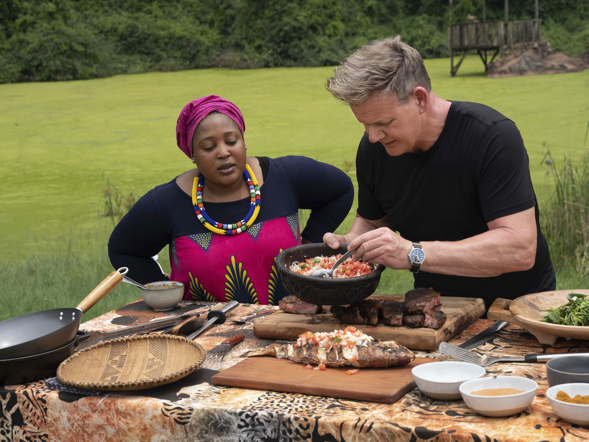Chef Zola Nene (L) observes as Gordon Ramsay tops grilled Snapper with ushatini, a combination... [Photo of the day - September 2020]