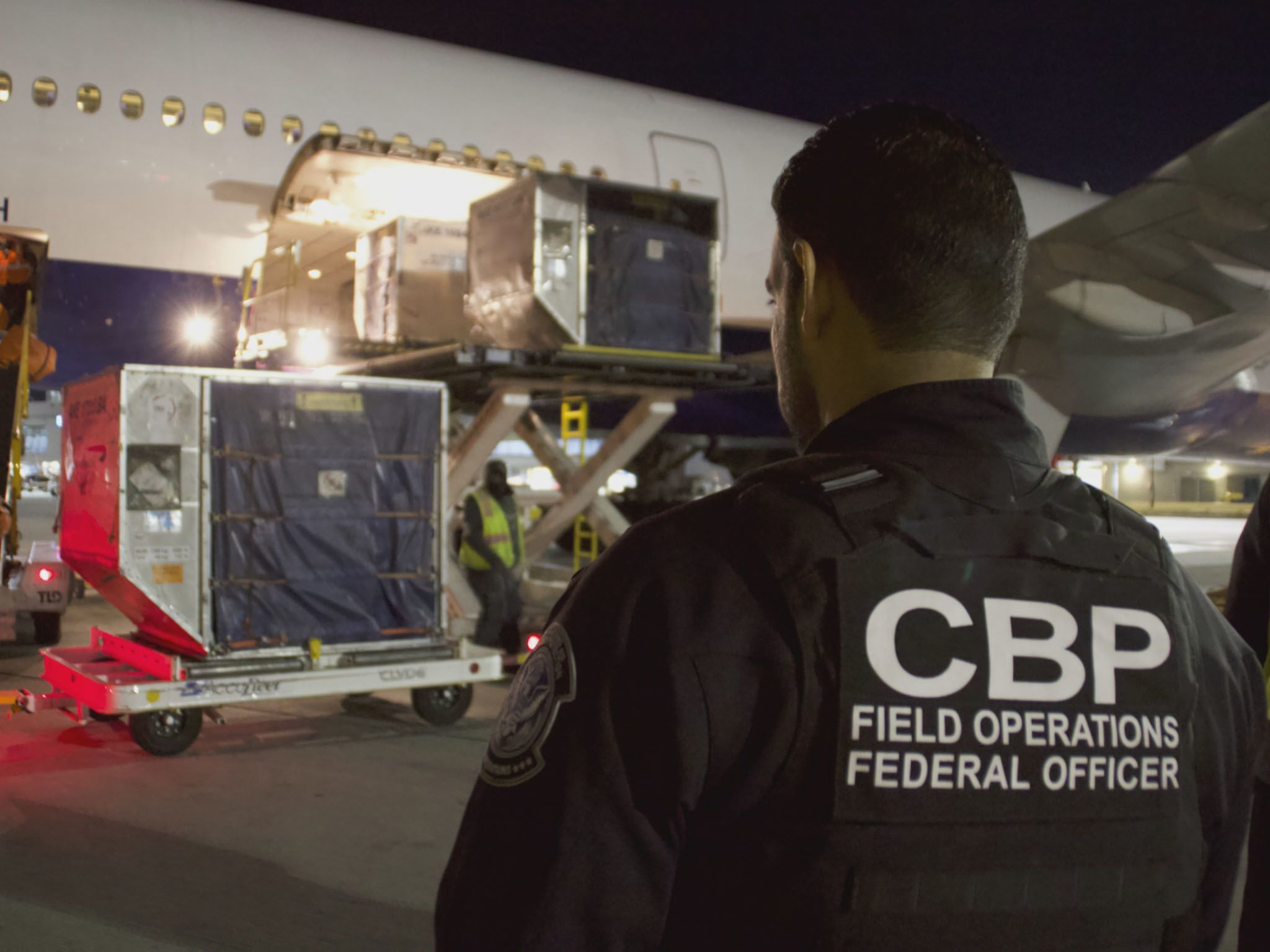 ATECT Officer Miguel Morales watches cargo unload. This image is from To Catch A Smuggler. [Photo of the day - March 2021]