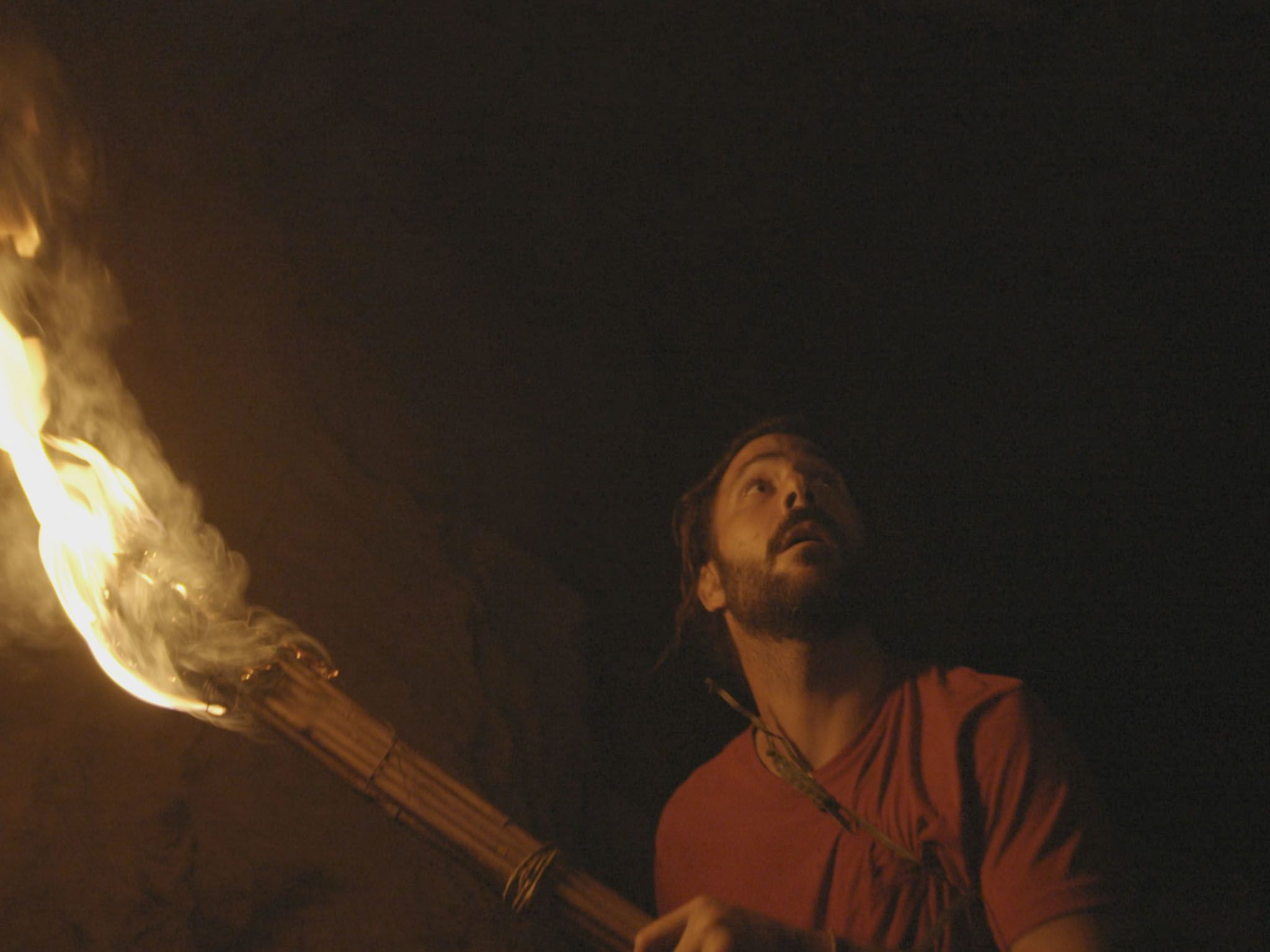 Hazen holding a fire torch in a dark cave. (National Geographic/Alex Holden). This image is from... [Photo of the day - April 2021]