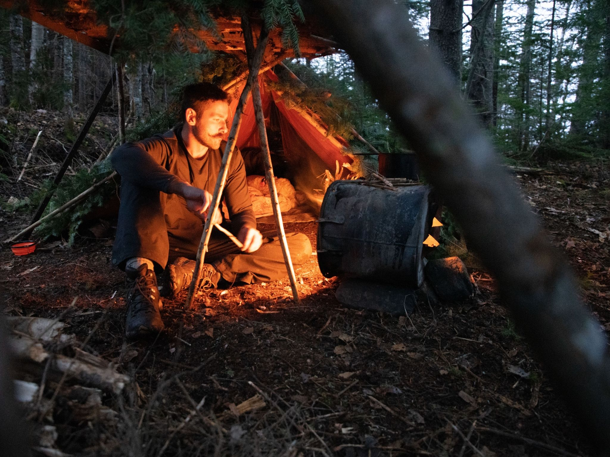 Dane tends to the fire as Willow sleeps in the shelter.  This is from Called to the Wild. [Photo of the day - August 2021]