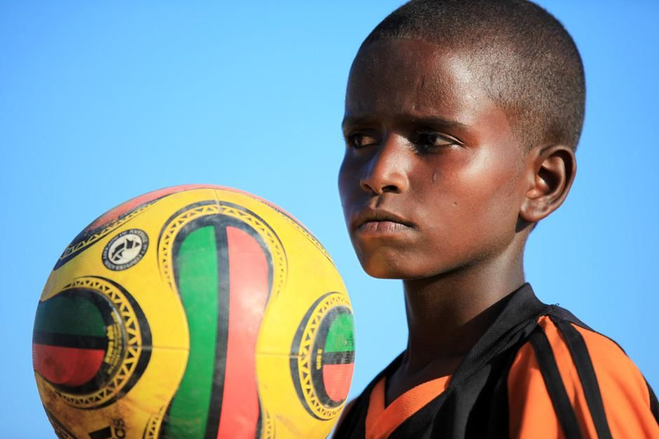 Somalia: A close-up of a Somali boy holding up a football while his eyes catch something outside... [Photo of the day - October 2012]