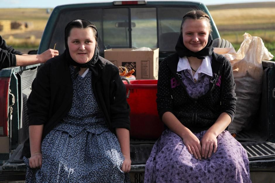 King Colony, Montana: Lori Hofer and Megan Hofer sitting on the back of a truck on carrot... [Photo of the day - December 2012]