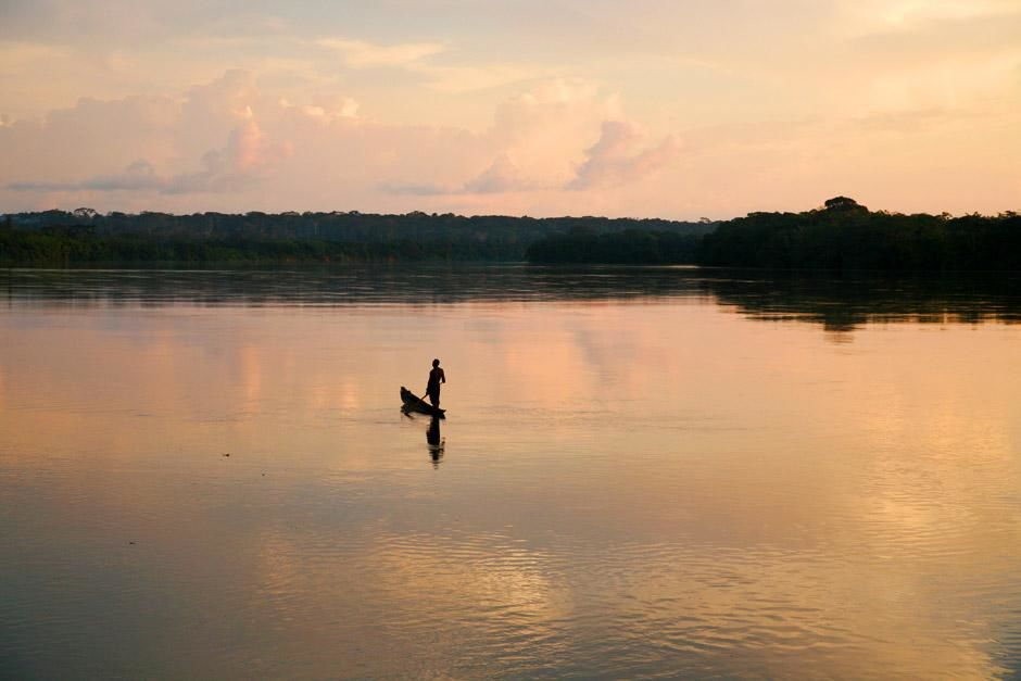 Central African Republic: A lone man on his boat sits in calm waters. This image is from My... [Photo of the day - December 2012]