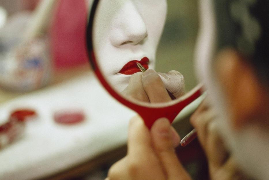 إحدى فتيات الغايشا تنظر في المرآة لتضع أحمر الشفاه... [Photo of the day - أكتوبر 2011]