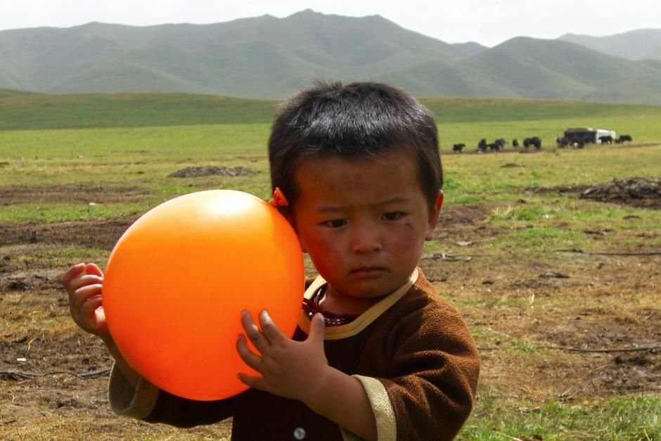 Young nomad plays with a balloon given to him as a gift from Paul Merton. This image is from... [Photo of the day - مارس 2013]