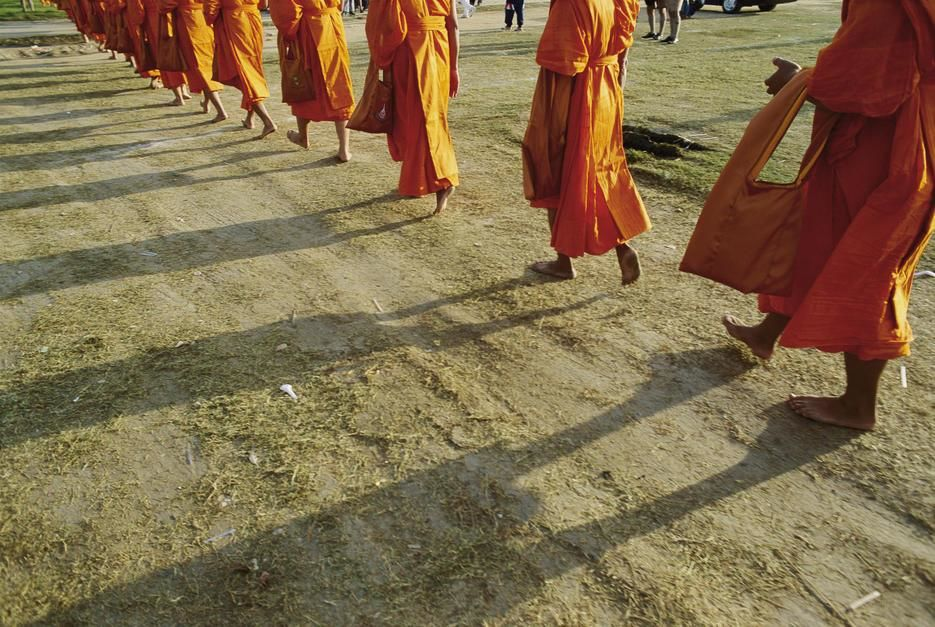 A group of Buddhist Monks walk single file down a dirt road. Thailand. [Photo of the day - July 2011]