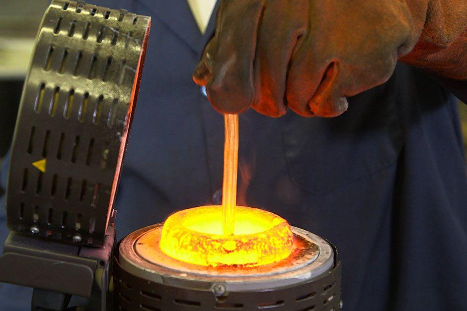 Hayden, Idaho, USA: il fabbro Gomer Daves Jr. rimescola l'oro fuso in una forno con fusione a... [Foto del giorno - December 2013]