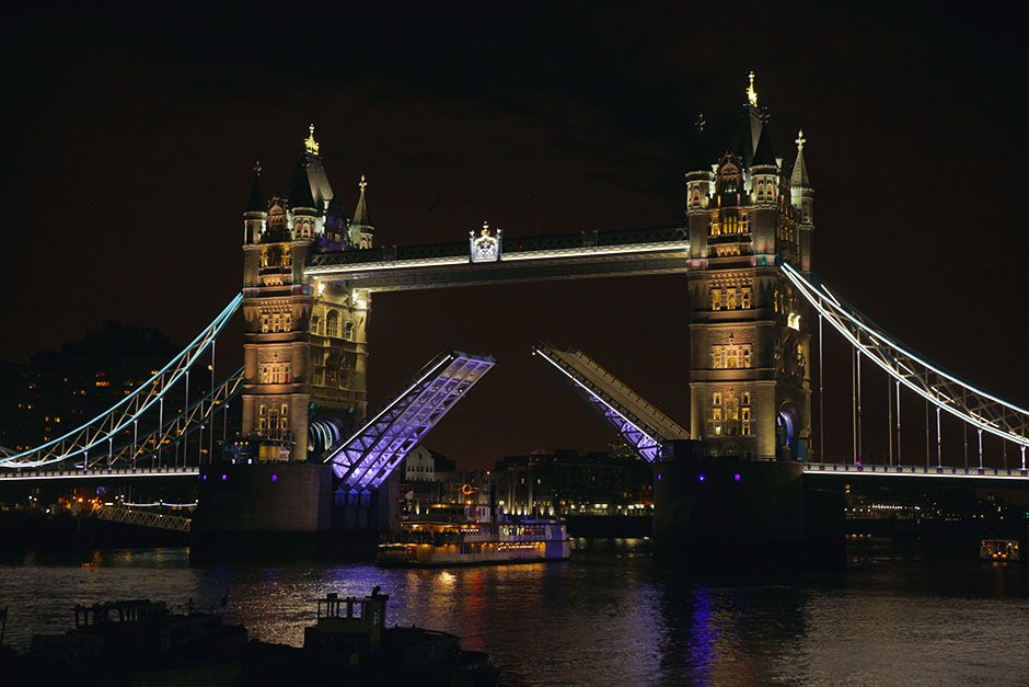 London, England: The Tower Bridge partially open at night.
