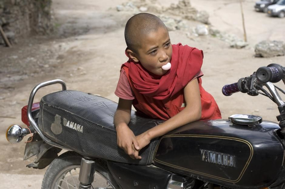 A young monk blows a chewing gum bubble leaning on a Yamaha, Hemis Monastery, Ladakh District. [Photo of the day - January 2012]