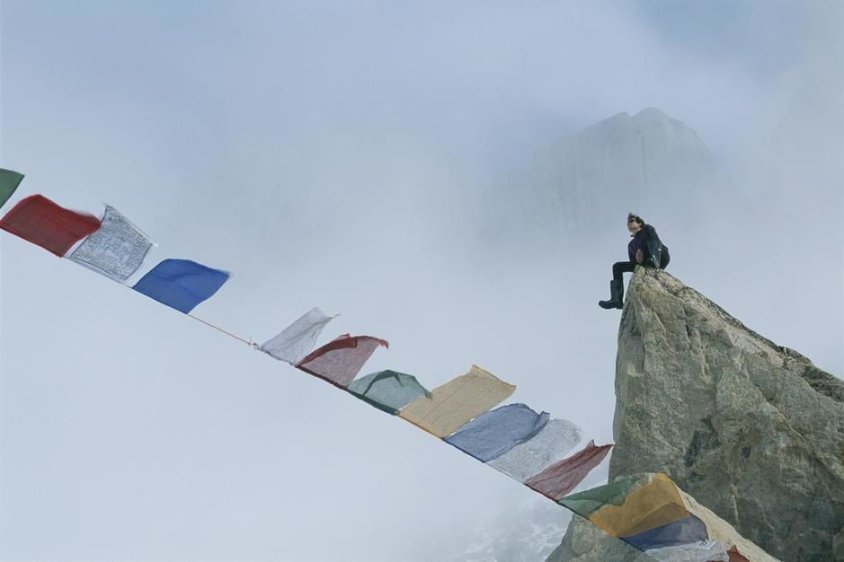 Mountain climber Alex Lowe sits on a rock near Tibetan prayer flags on Baffin Island. Canada. [Photo of the day - August 2011]
