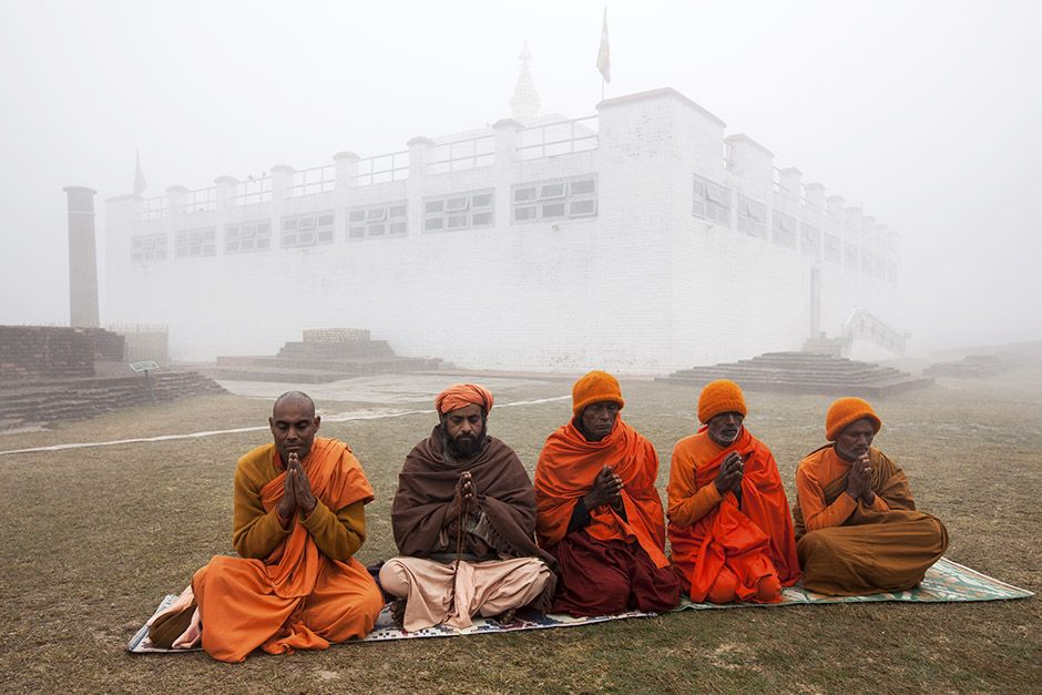 In Lumbini, Nepal, the birthplace of The Buddha. Pilgrims pray by the Asokan Pillar on a foggy... [Photo of the day - آوریل 2014]