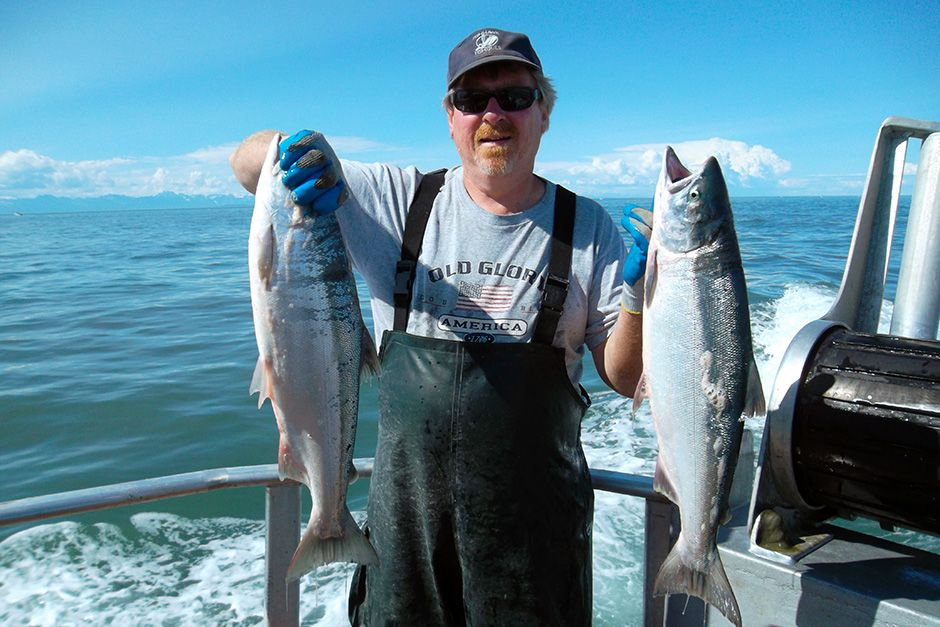Deckhand Lance Alldrin holding two fish for the camera. This image is from Alaska Fish Wars. [Photo of the day - May 2014]