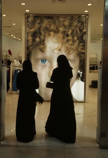 Two veiled Arabic women face an advertising poster in a shopping mall in Doha. [Photo of the day - March 2011]