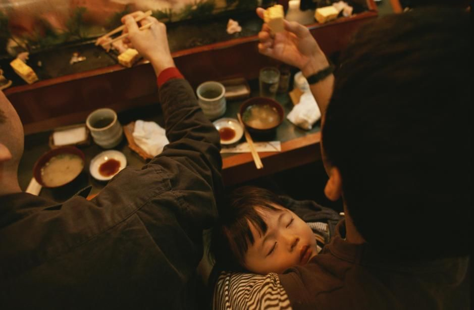 A man holds his sleeping son while eating at a sushi restaurant in Tokyo. [Photo of the day - March 2011]
