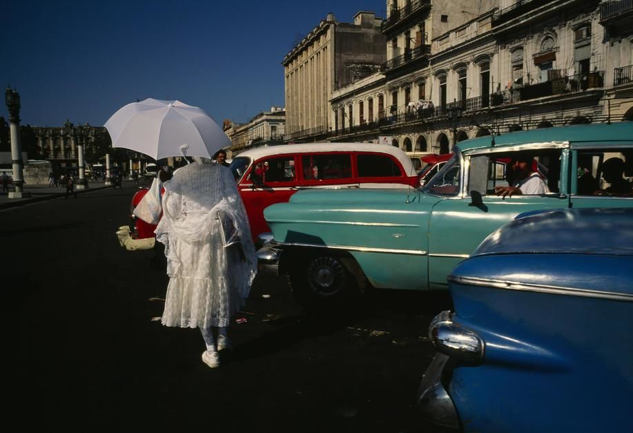 A woman in formal dress carrying an umbrella passes by vintage cars in Havana. [Photo of the day - April 2011]