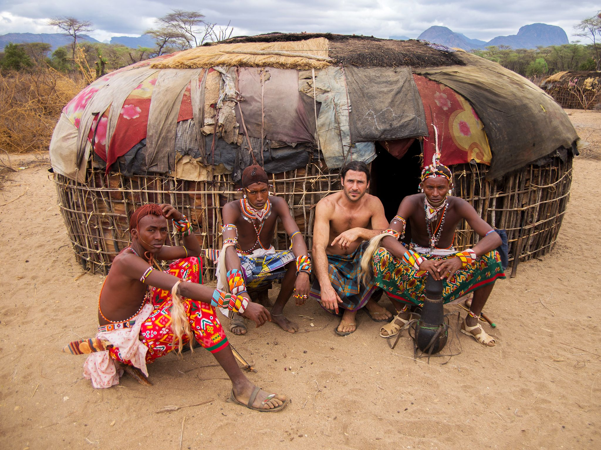 Mpagas, Kenya: Hazen Audel sitting outside Samburu of a hut with three Samburu warriors. This... [Photo of the day - سپتامبر 2014]