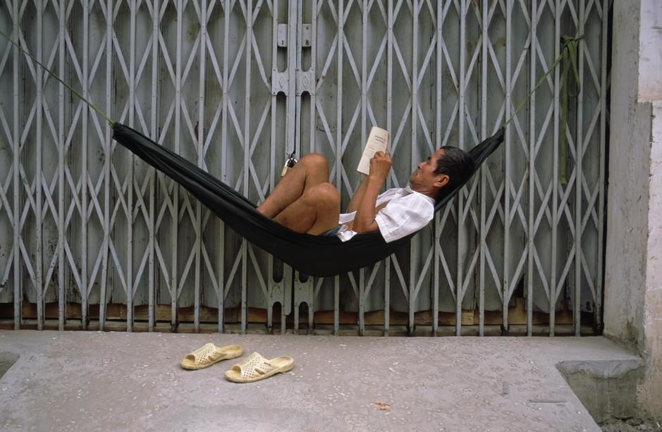 A man in a hammock reads a book outside the closed door of a shop in Saigon. [Photo of the day - April 2011]
