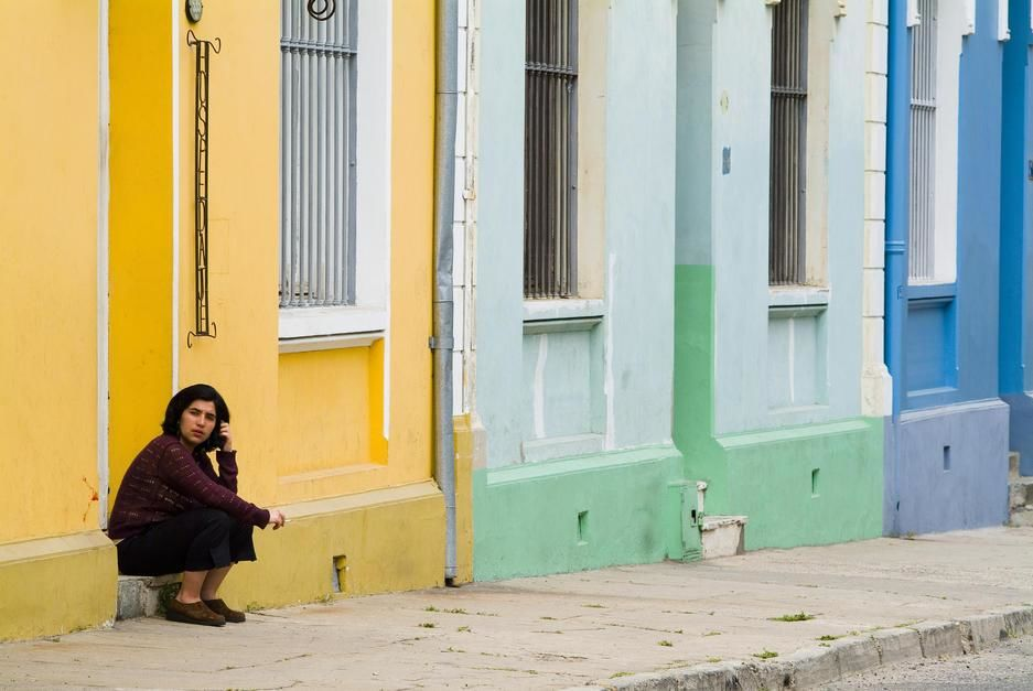 A woman sits on the stoop of an orange building in Valparaiso. [Photo of the day - April 2011]