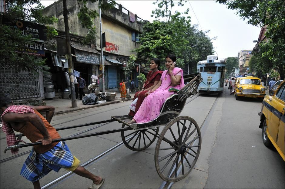 A woman talks on a mobile phone while riding a human-powered rickshaw in Kolkata, West Bengal. [Photo of the day - April 2011]