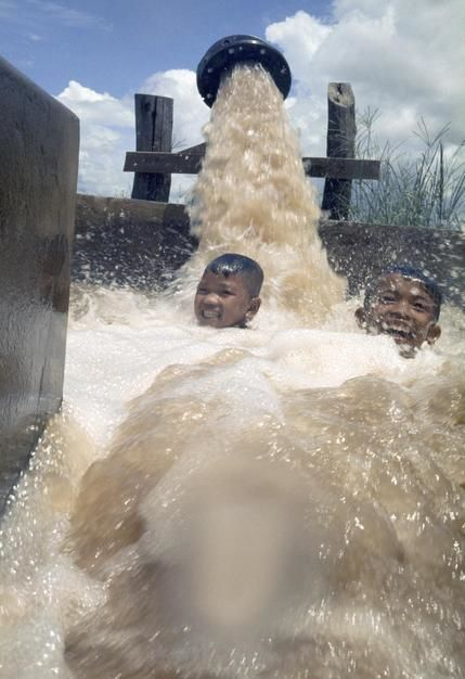Boys laugh while being drenched with pumped Mekong River water. [Photo of the day - می 2011]