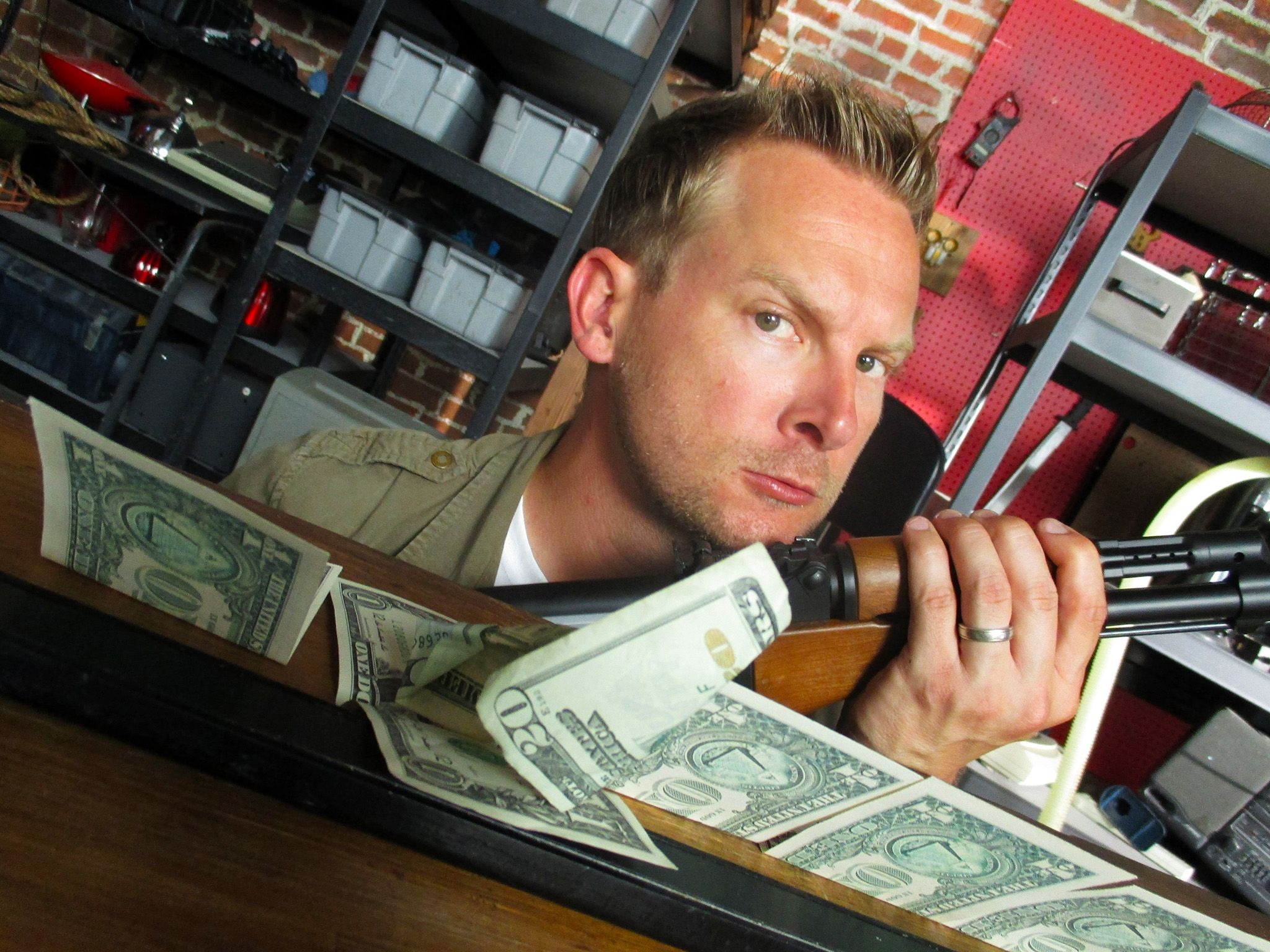 Los Angeles, CA.: In the workshop, Brian poses with a rifle next to a line of bills and a... [Photo of the day - April 2015]