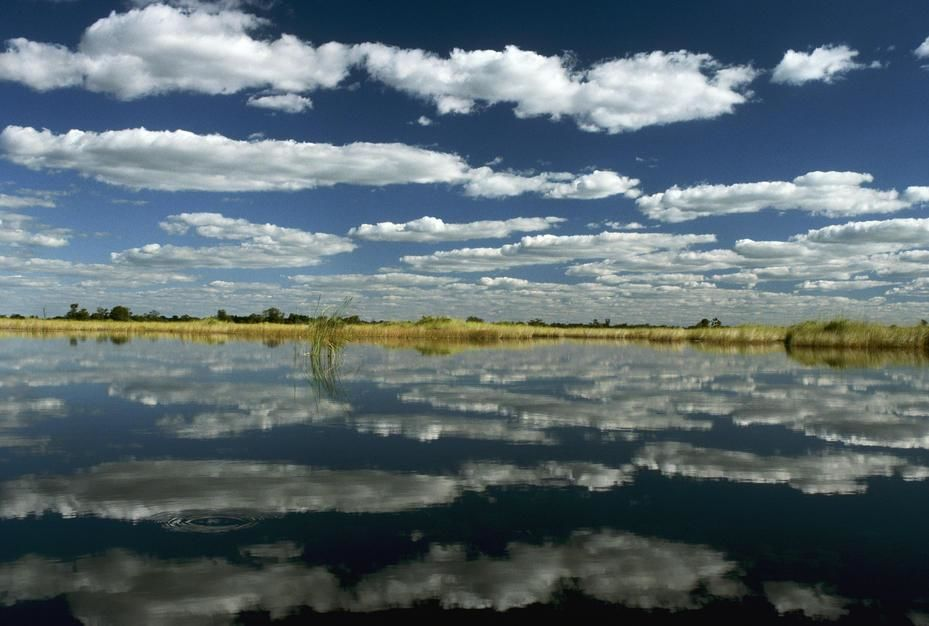 Clouds over the Okavango Delta reflect from Qogana Lagoon. Unlike the seasonally dry outer... [Photo of the day - August 2011]