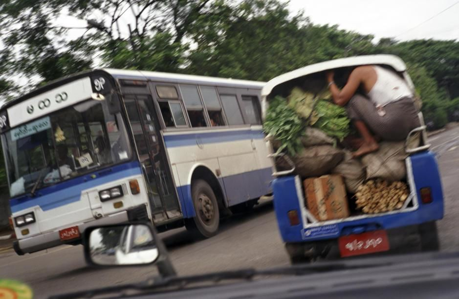 A man crouches down inside the back of a truck carrying vegetables in Rangoon. [Photo of the day - May 2011]