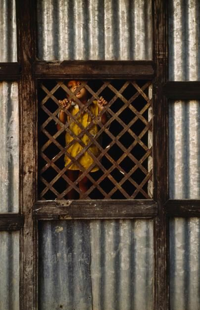 A young boy in a poor rural village looks through a lattice window. [Photo of the day - June 2011]