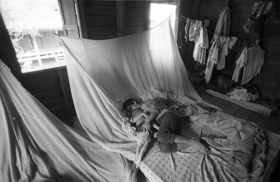 Mother and daughter snuggle together in bed while laundry hangs to dry. [Photo of the day - July 2011]