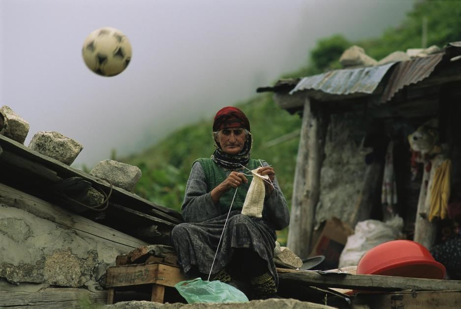 A soccer ball flies over the head of a woman who is knitting outdoors. Turkey. [Photo of the day - August 2011]