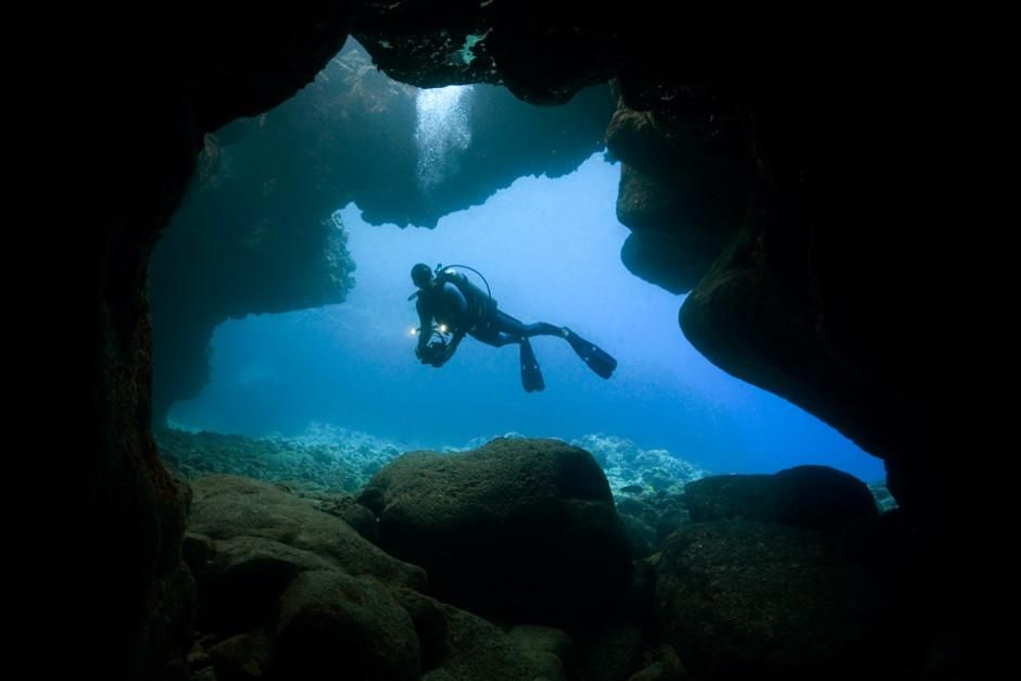 A scuba diver explores a cave near Kona, Hawaii. This image is from Most Amazing Photos. [Photo of the day - February 2012]