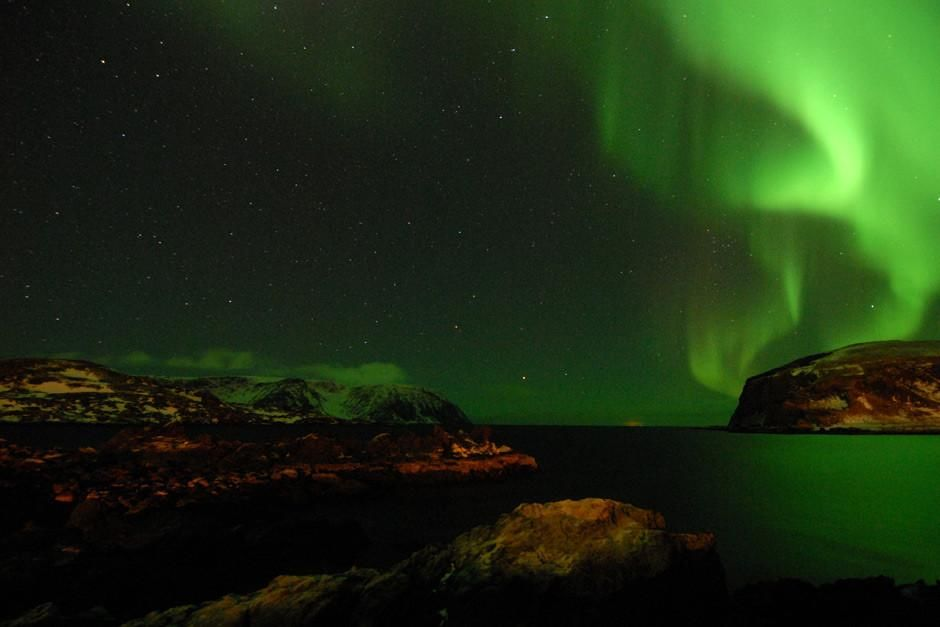Norway: Northern Lights (Aurora borealis) paints the sky and water neon green. 