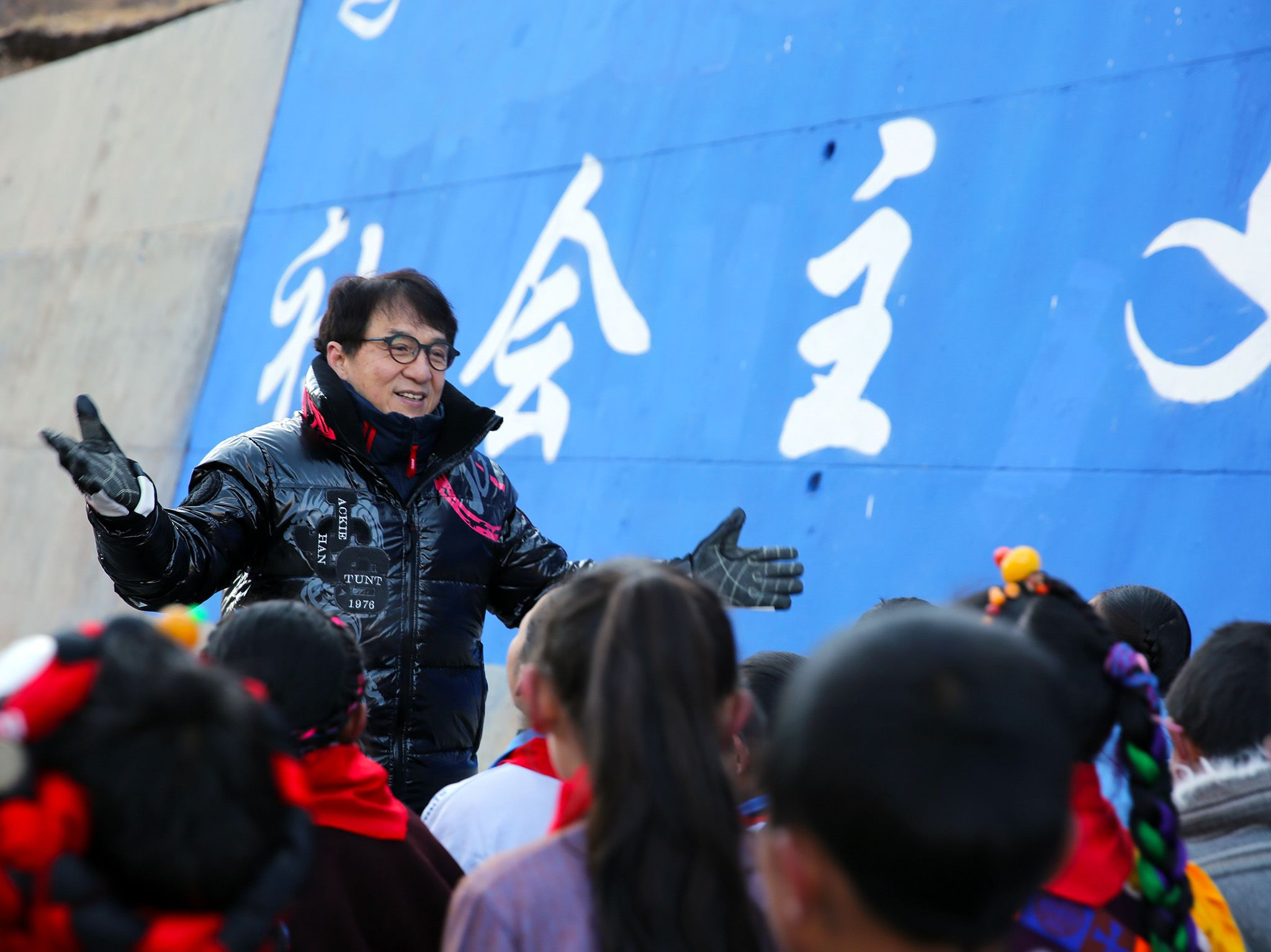 Zadoi, China:  Jackie Chan facing children, conducting their song. This image is from Jackie... [Photo of the day - September 2018]