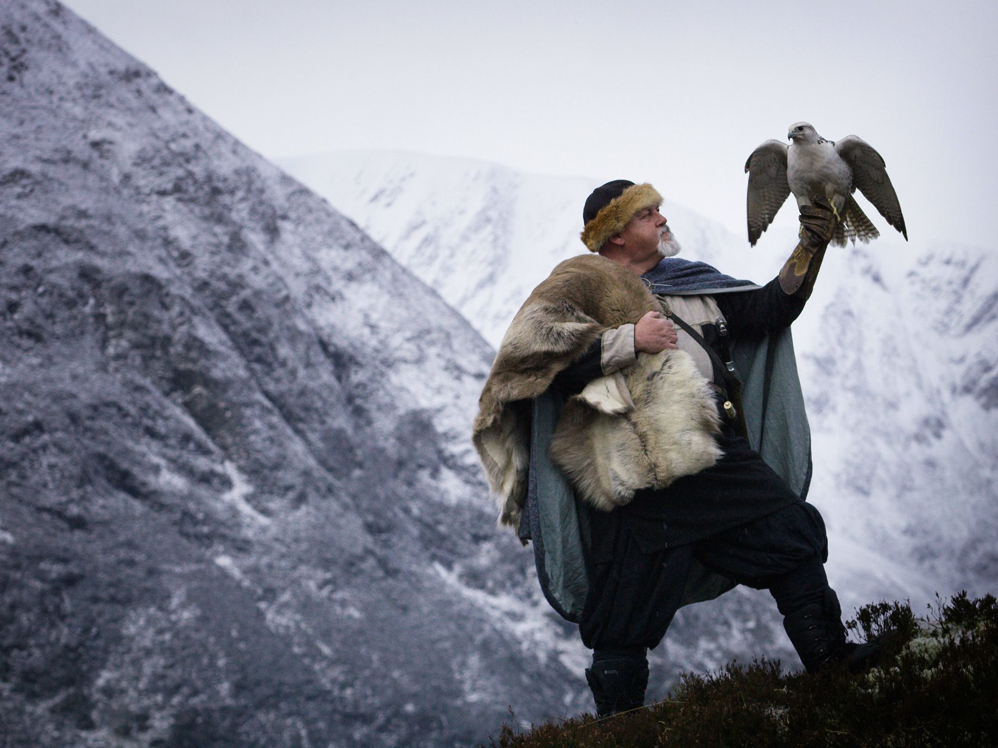 A Viking reenactor and a Gyrfalcon pose in snowy landscape at Alladale Wilderness reserve in... [Photo of the day - March 2019]