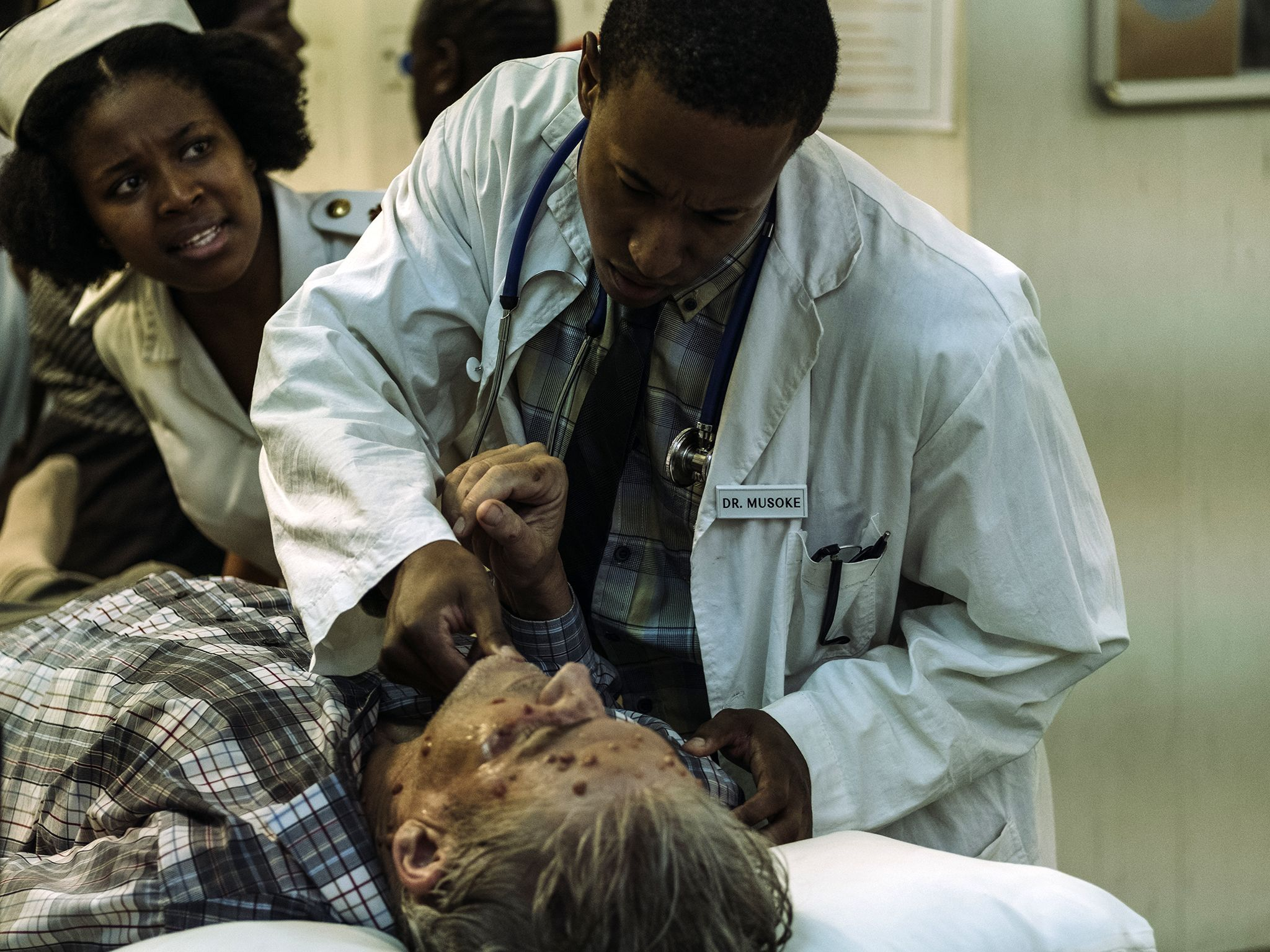 Dr. Musoke (Bohang Moeko) and a nurse tend to Charles Monet (Neil McCarthy) and wheel him into... [Photo of the day - May 2019]