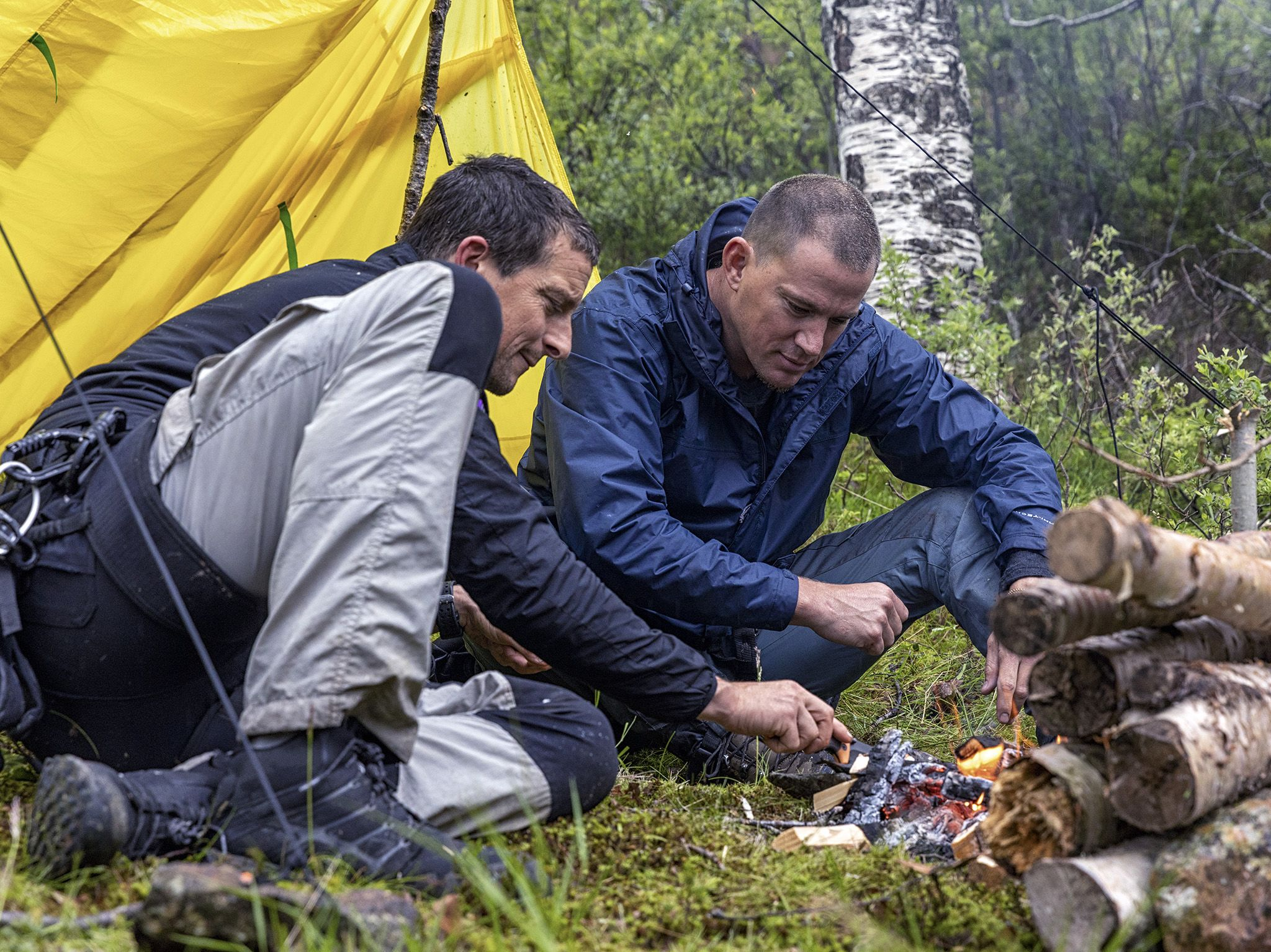 Norway:  (L to R) Bear Grylls and Channing Tatum build a fire next to a lake. This image is from... [Photo of the day - نوامبر 2019]